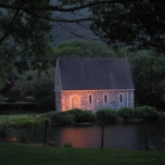 The chapel in Gougane Barra lit by a setting sun.