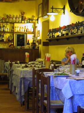 A woman waiting for a dinner companion at a small restaurant in Rome.