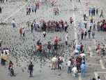 Tourists collecting pigeons on the plaza in front of the Basilica di San Marco.